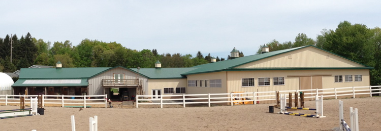Rear view of new arena and clubhouse attached to existing stall barn