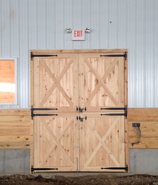 Wooden double doors at walkway leading to stall barn